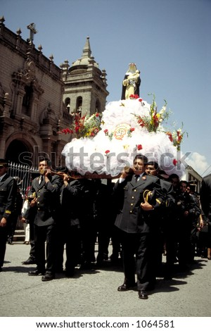 Policemen carry a statue of Our Lady through the streets of Ayacucho, a colonial town in the central highlands of Peru. - stock photo