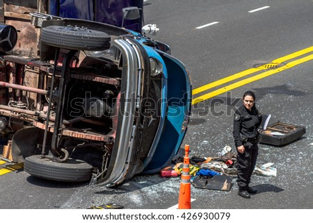 Policewoman in front of a dump truck directs traffic after a traffic accident. Buenos Aires, Argentina. October 30, 2014.