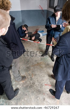 Policewoman interviewing bystanders and witnesses for their statement about a murder having taken place at the crime scene behind her - stock photo