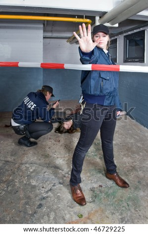 Policewoman making a stopping gesture with a blood stained outstretched hand to keep a bystander away from the perimeter of a crime scene