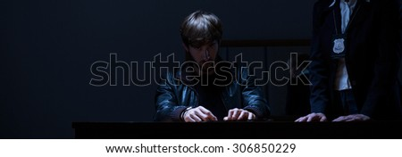 Policewoman questioning man in a dark room - stock photo