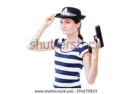 Policewoman touching her police cap and holding a gun - isolated on white. - stock photo