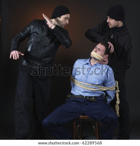 Policman and two thiefs.  they have captured him and tied him down. Dark background. - stock photo