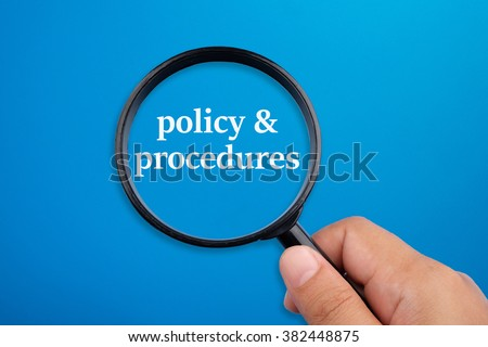 Policy & procedures. Hand holding magnifying glass focusing on the words. - stock photo