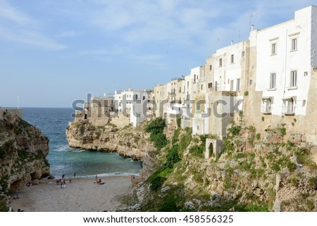 Polignano a mare, Italy - 23 June 2016: people walking on the beach of the scenic small town built on rocks in Puglia, Italy