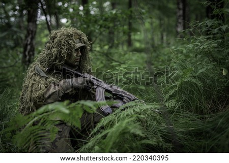 Polish camouflaged soldier with assault rifle in forest at defending position - stock photo