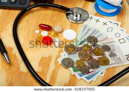 Polish money with stethoscope on a wooden table