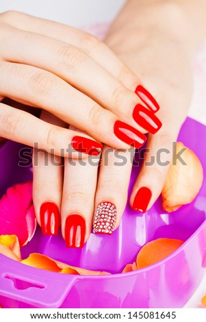 polish on fingers with red nails - stock photo