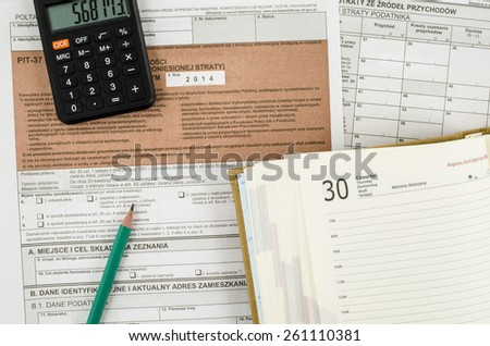 Polish tax form with pencil, calendar and calculator - stock photo