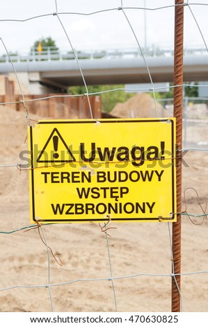 Polish yellow warning sign on a grid fence saying: Look out, construction area, entry forbidden.