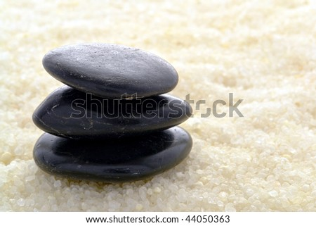 Polished black massage stone cairn on bed of natural sea bath salts in a spa