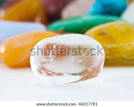 Polished clear transparent quartz gemstone in front of gemstone collection - stock photo