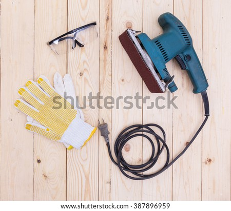 polishing machines with glove and Splinter glasses on wood table - stock photo