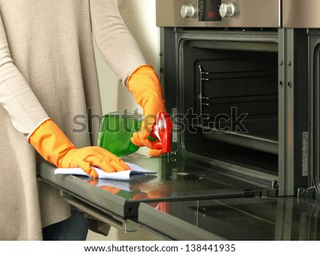Polishing the oven with rubber and special spray - stock photo