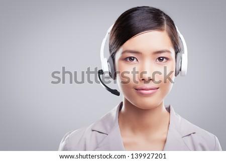 Polite Asian customer service representative in close-up. - stock photo