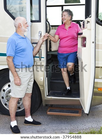 Polite senior man helps his wife down the stairs of their motor home. - stock photo