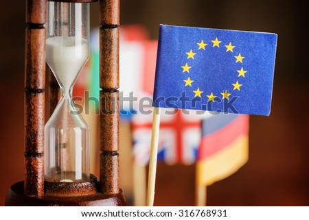 Political concept with flag of the European Union (EU). Time is running out. Closeup view of hourglass and flag of the European Union (EU). Flags of European countries in background.