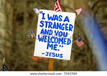 Political sign with with religious tone at a pro-immigration rally in USA - stock photo