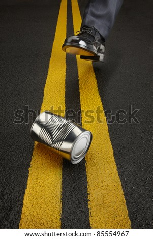 Politician kicks a shiny, dented can down the road toward the camera - stock photo