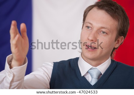 politician man speaking - france flag in background - stock photo