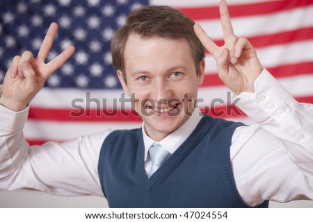 politician with victory signs over american flag - stock photo