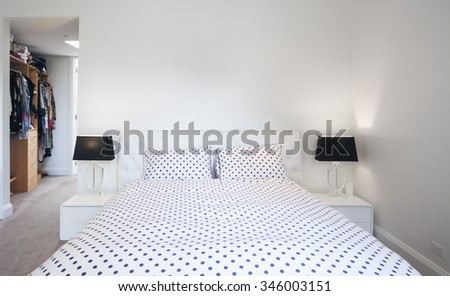 Polka dot duvet cover in contemporary black and white bedroom scheme in Australian home - stock photo