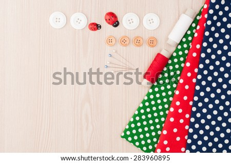 Polka dot fabric for sewing and accessories for needlework on wooden background. Spool of thread, buttons, sewing supplies. Set for needlework top view - stock photo