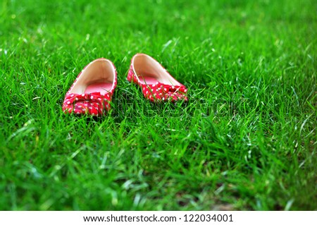 Polka-dot flat shoes left on a grass - stock photo