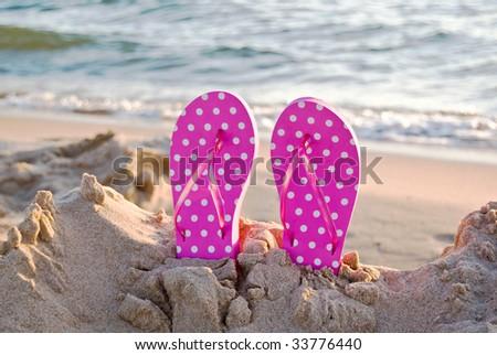 polka dot flip-flops in sand - stock photo