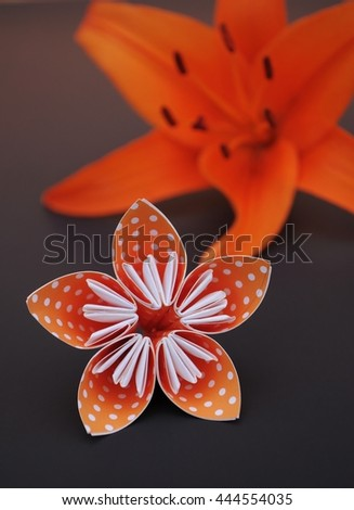 Polka dotted origami flower next to a real lily flower. - stock photo