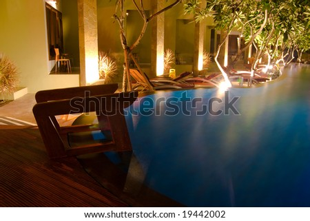 Poll ladder and chairs by the swimming pool in the night - stock photo
