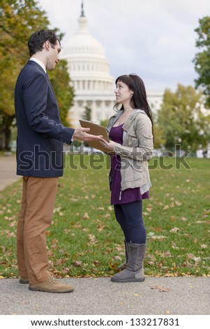 Poll-taker/Canvasser Talking To Businessman In Front Of US Capitol - stock photo