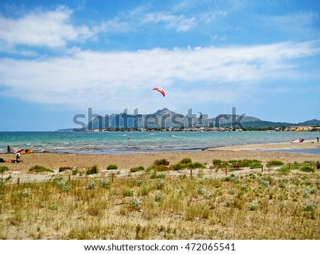 Pollenca, Majorca, Spain - June 28, 2008: Kite surfers at bay of Pollenca - somewhere between Pollenca and Alcudia, view towards peninsula Victoria, north of Majorca - natural beach in front
