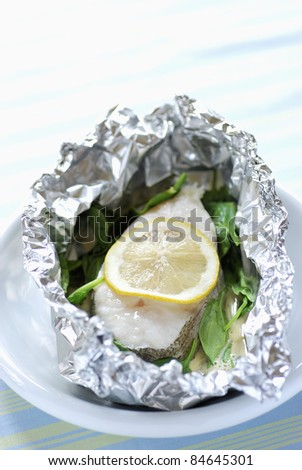 Pollock and lemon cooked in aluminium foil - stock photo