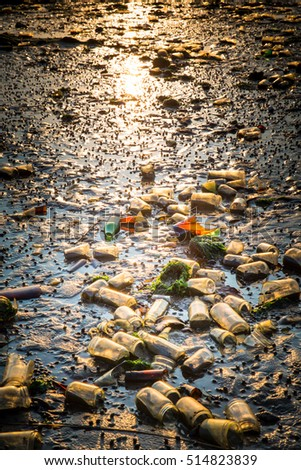 Polluted beach covered in old glass bottles from landfill at Dead Horse Bay in Brooklyn NY