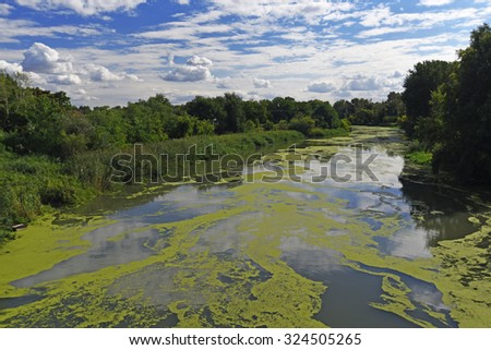 Polluted river and clouds on blue sky  - stock photo