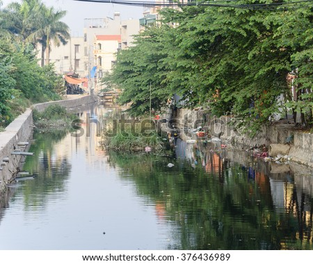 Polluted river and dirty sewer in an urban area in Hanoi. Polluted water and garbage are serious subject of Vietnam - stock photo