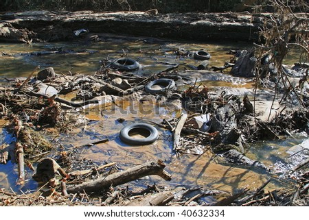 Polluted river bed full of junk that should not be. - stock photo