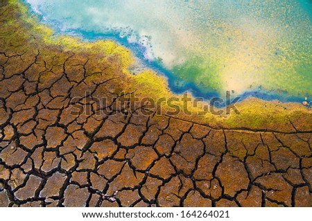 Polluted water and cracked soil during drought. - stock photo