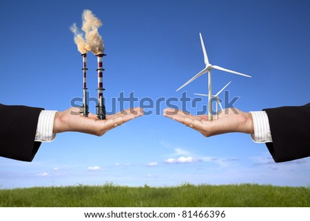 pollution and clean energy concept. businessman holding windmills and refinery with air pollution - stock photo