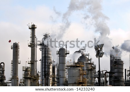 Pollution arches over the towers of a large oil refinery. - stock photo