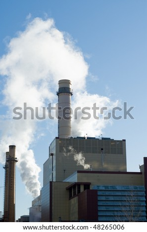 Pollution bellowing from a refinery smoke stack - stock photo