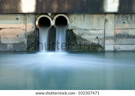 Pollution drain flowing stream to a river - stock photo