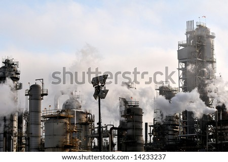 Pollution drifts across the industrial apparatus of a large oil refinery.