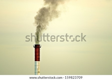 Pollution from single factory chimney at sunset - stock photo