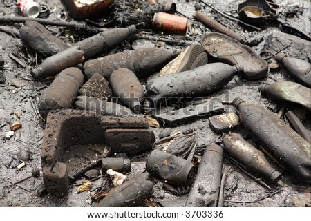 Pollution in Havana bay (Cuba). Plastic bottles and trash covered with black oil. - stock photo