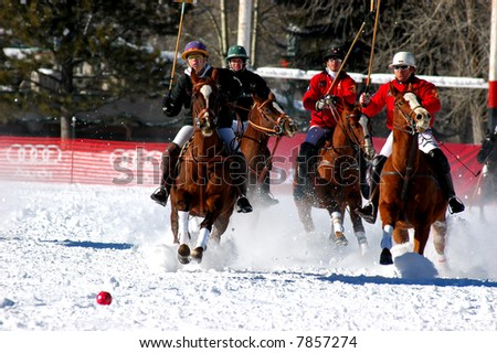 Polo players at full gallop in world championship snow polo game - stock photo