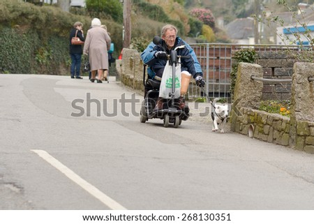 POLPERRO, CORNWALL, ENGLAND - MARCH 16: Elderly man on mobility scooter walking Jack Russell Terrier dog down road, shown on 16 March 2015 in Polperro - stock photo