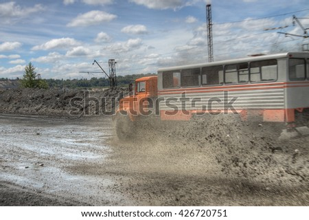 Poltava Region, Ukraine - June 26, 2010: Mining crew bussplashes driving at high speed along the opencast with mud splashes