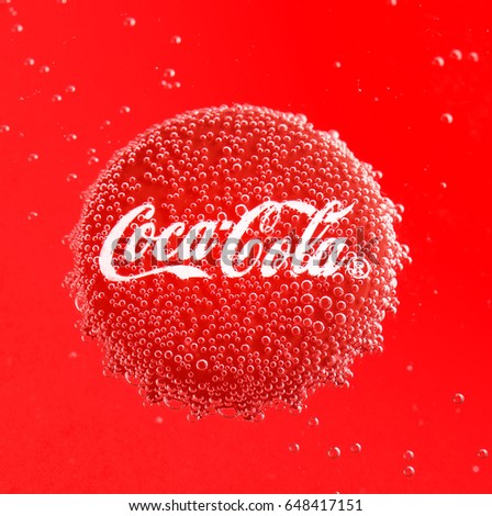 POLTAVA, UKRAINE - APRIL 7, 2017: Coca Cola Cap.Coca Cola Cap in bubbles on a red background.